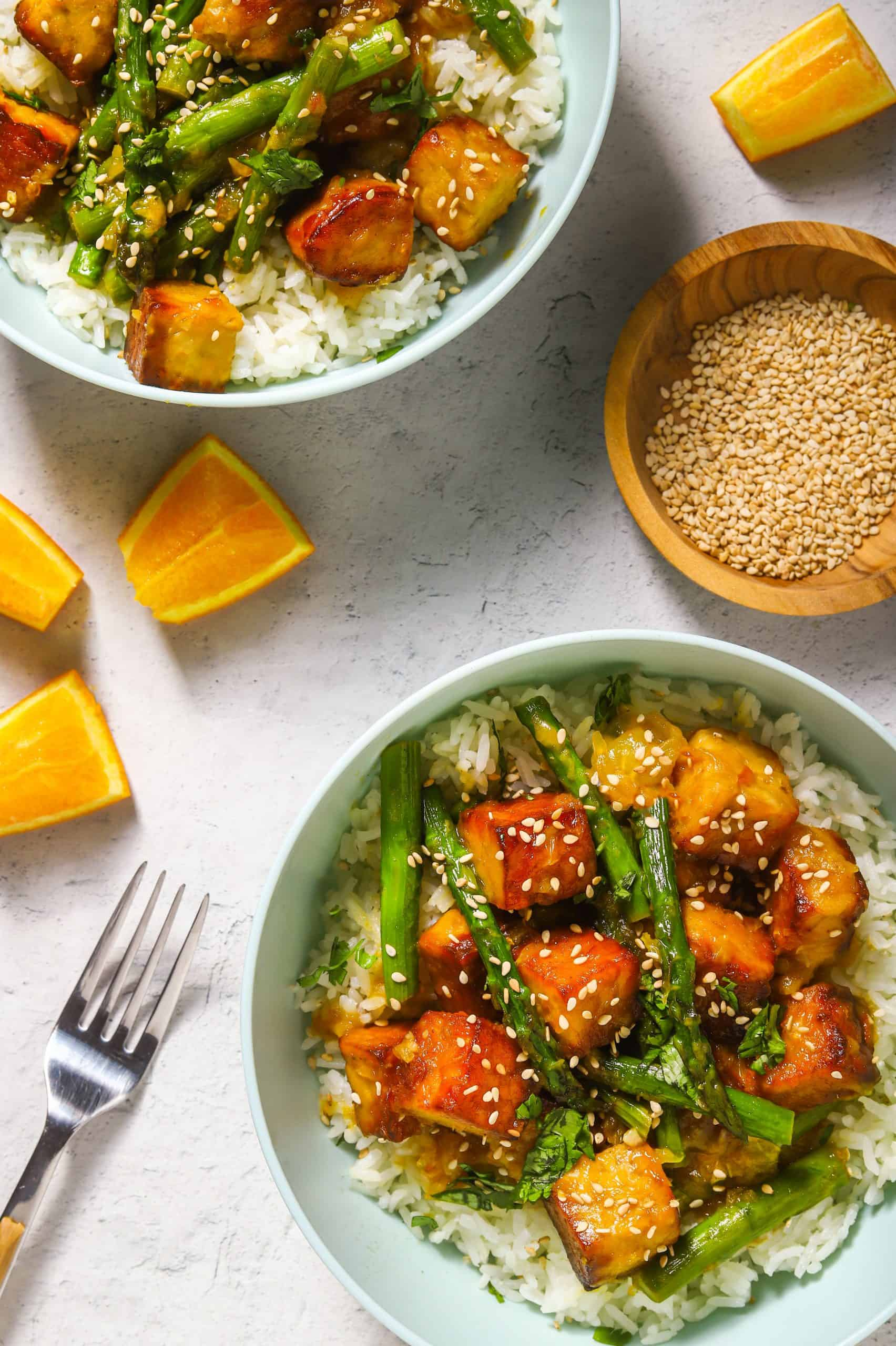 orange tempeh with aspargus in bowls with rice