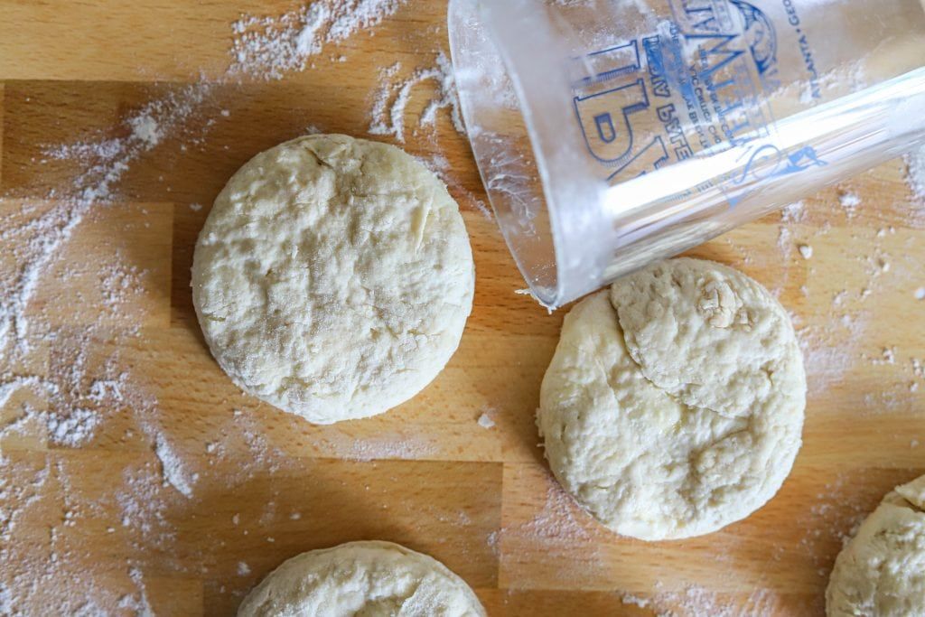 cutting out homemade biscuits with a glass