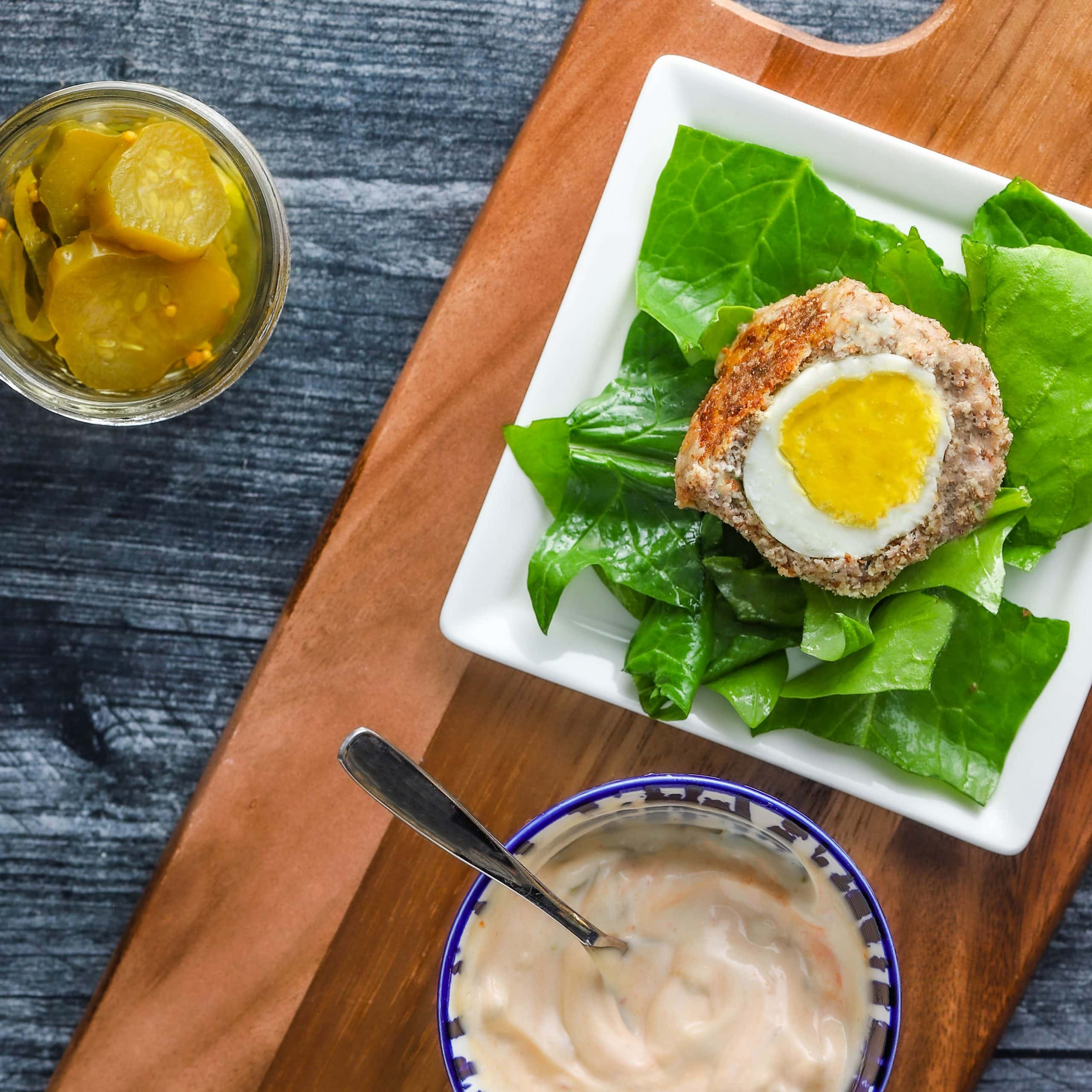 keto scotch eggs on plate with sauce