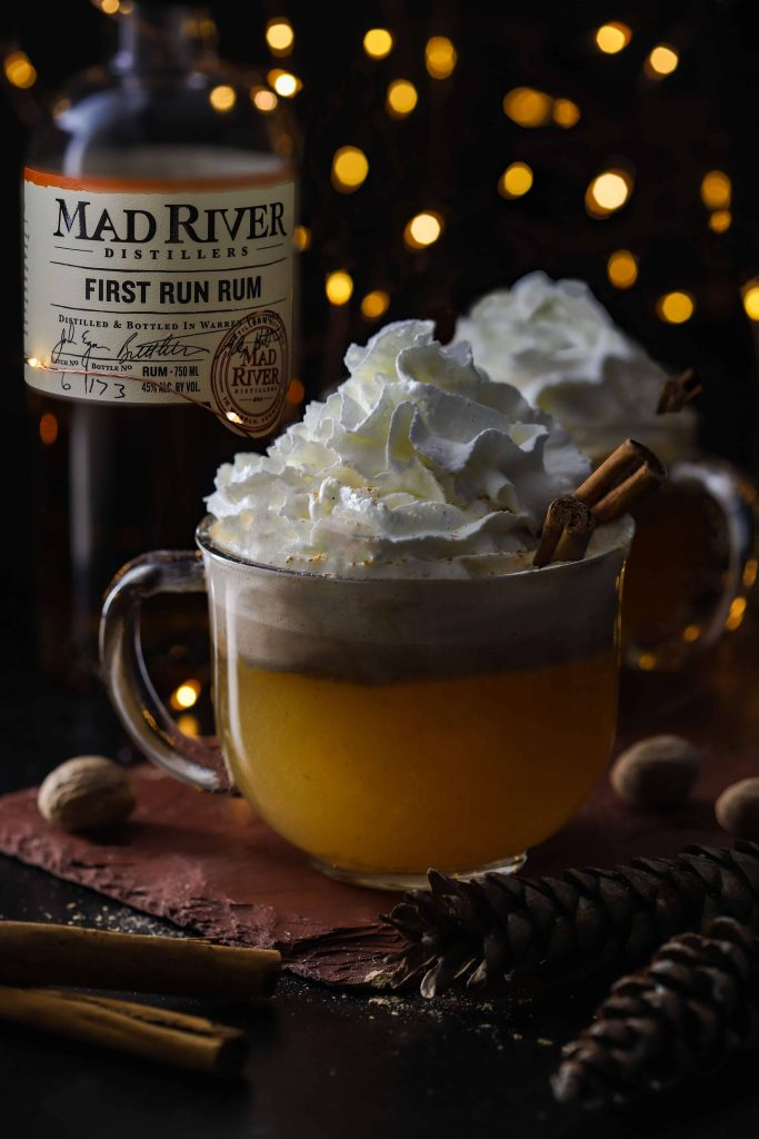 mugs of hot buttered rum with whipped cream