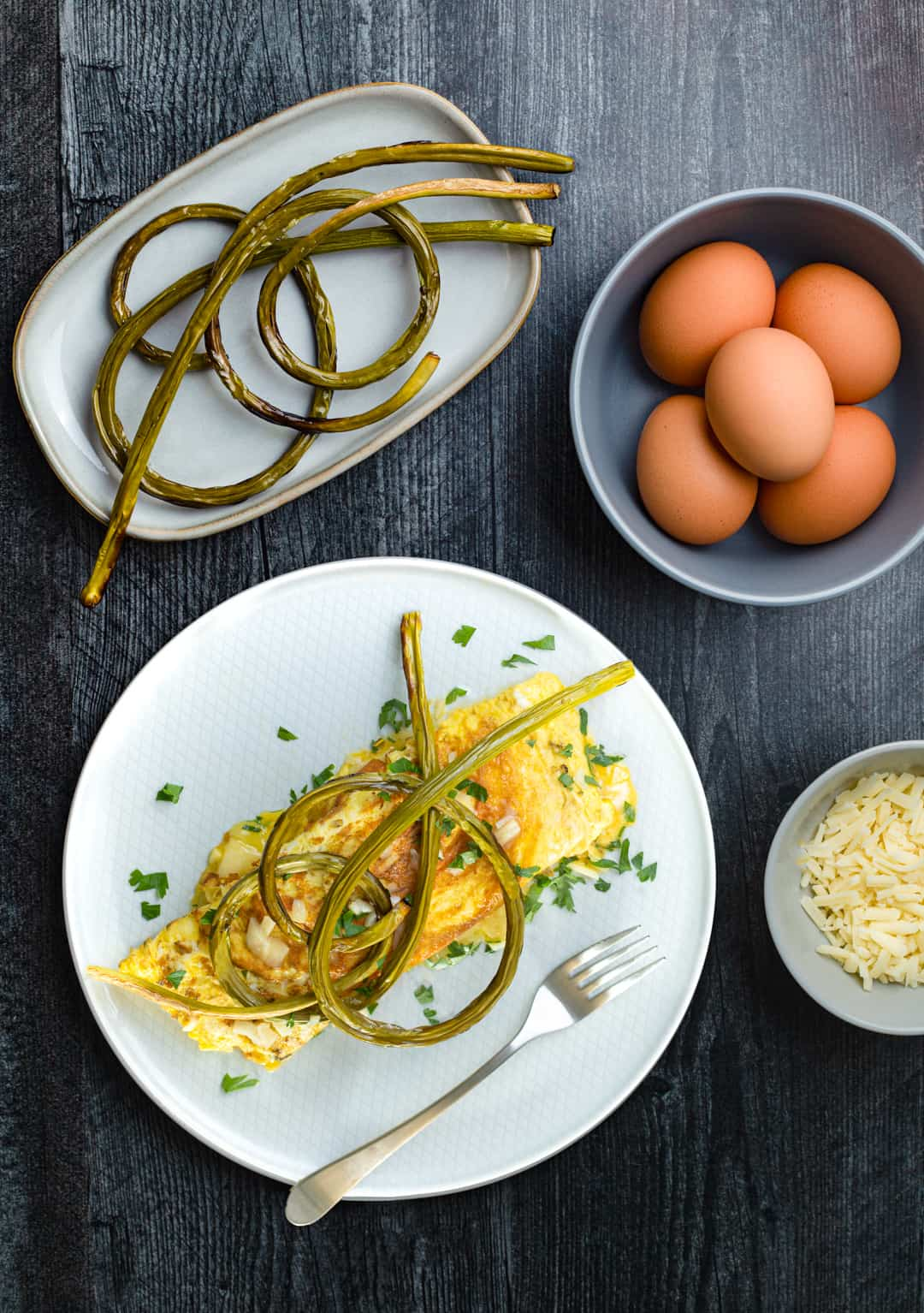 roasted garlic scapes on top of an omelet with eggs and cheese