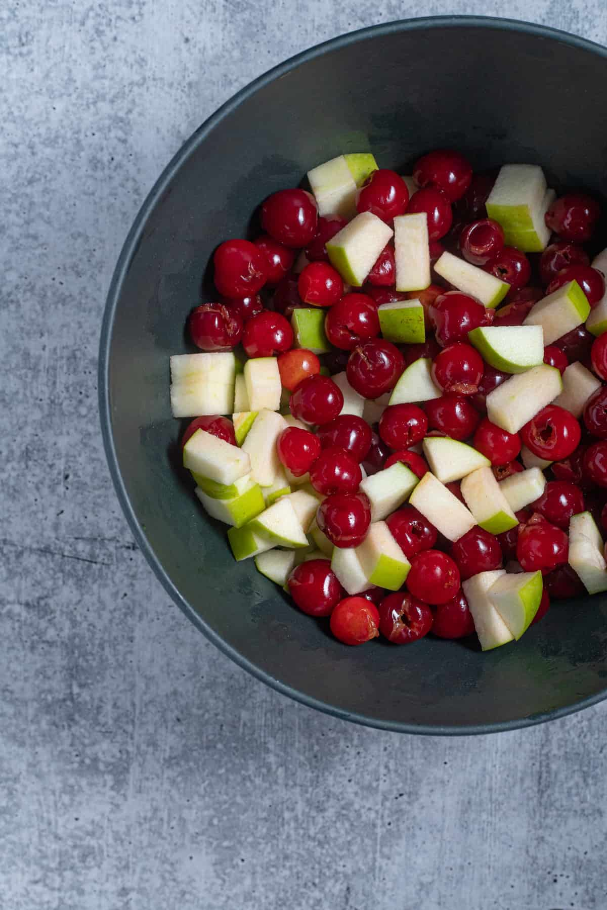 sour cherries and apples in a mixing bowl