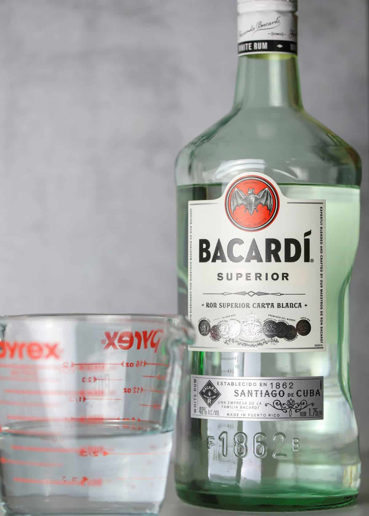 a bottle of bacardi rum and a measuring cup